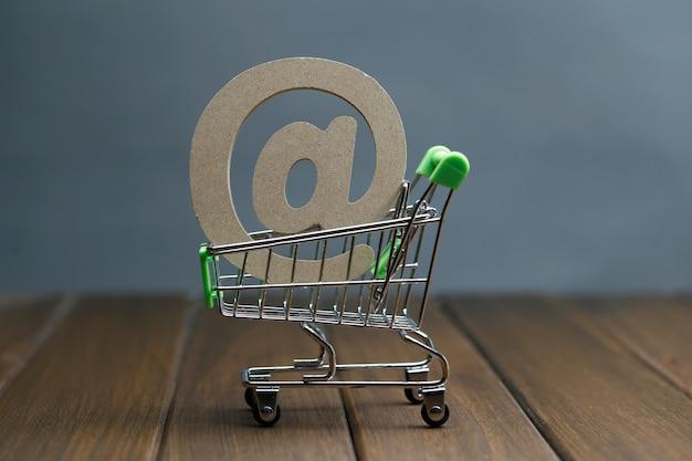 Símbolo de madeira @ no carrinho de compras, conceito de compras on-line