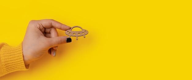 Símbolo de madeira ovni em mãos sobre fundo amarelo, maquete panorâmica
