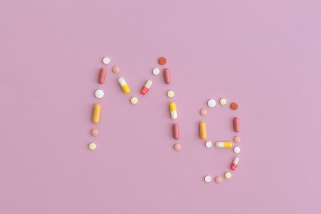 Símbolo de magnésio feito de comprimidos em fundo roxo