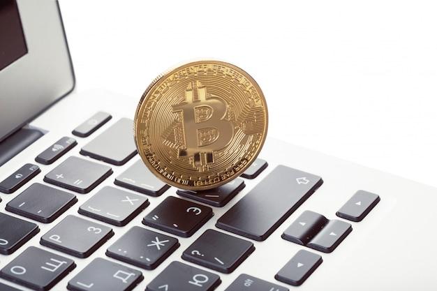 Símbolo de moeda física de bitcoin dourado no teclado