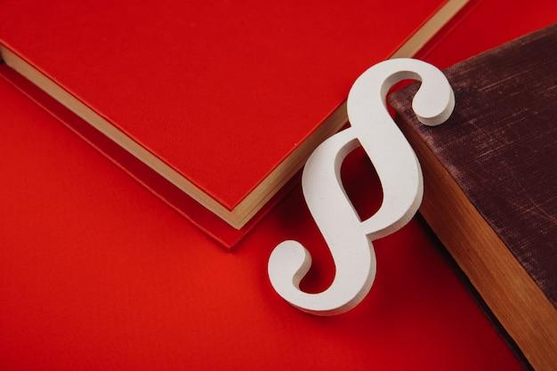 Símbolo de parágrafo branco com livros sobre fundo vermelho.