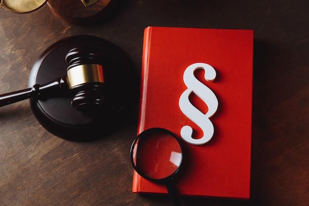 Símbolo de parágrafo branco em um livro vermelho e martelo do juiz no escritório do advogado