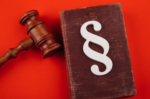 Símbolo de parágrafo e martelo em vermelho.