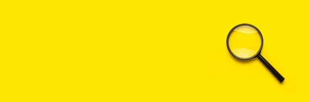 Símbolo de pesquisa de lupa de lupa na superfície amarela com espaço de cópia. bandeira.