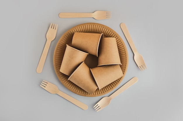 Símbolo de reciclagem como um símbolo conceitual, feito de copos de papelão descartáveis, pratos e garfos