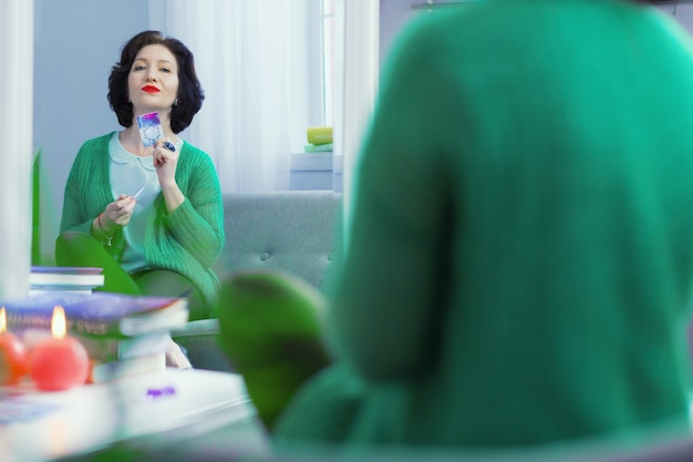 Símbolo de sorte. mulher alegre e simpática segurando um cartão na frente dela enquanto vê um símbolo da sorte