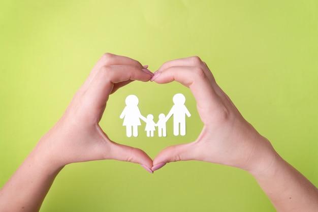 Símbolo de uma família amigável que protege a saúde, uma família de papel branco.
