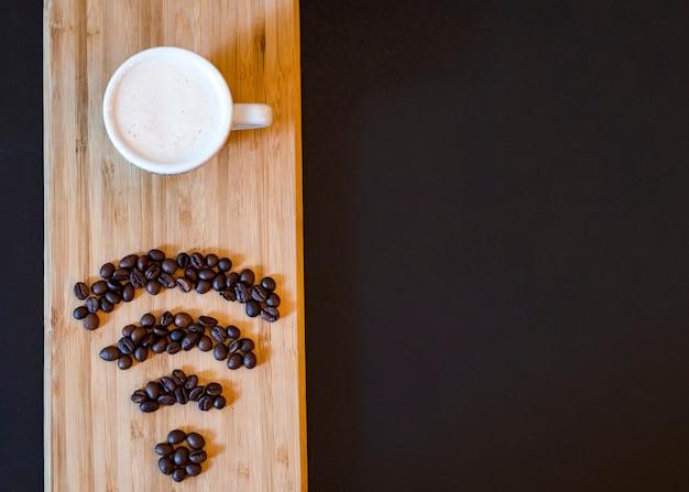 Símbolo de wifi de feijão de café com caneca na prancha de madeira