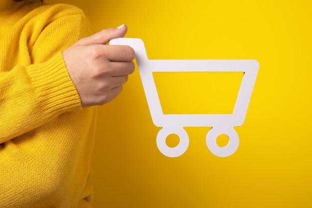 Símbolo do carrinho de compras disponível sobre fundo amarelo