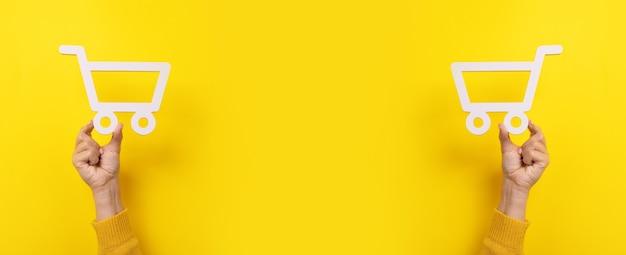 Símbolo do carrinho de compras em mãos sobre fundo amarelo, imagem panorâmica