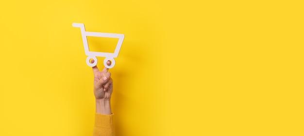 Símbolo do carrinho de compras em mãos sobre fundo amarelo