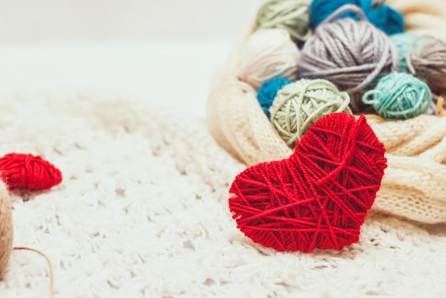 Símbolo do coração de malha e bolas de fio