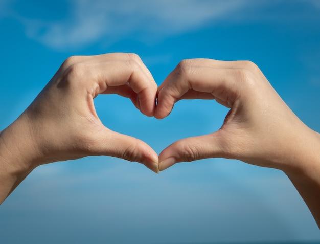 Símbolo do coração de mãos no céu azul. conceito de amor ou saúde.
