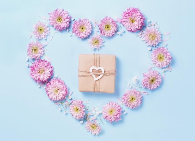 Símbolo do coração feito de flor rosa com caixa de presente em um fundo azul pastel
