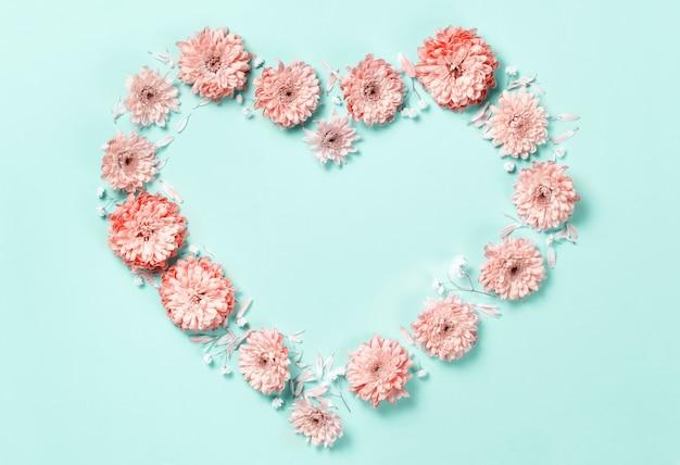 Símbolo do coração feito de flores de coral em um fundo pastel