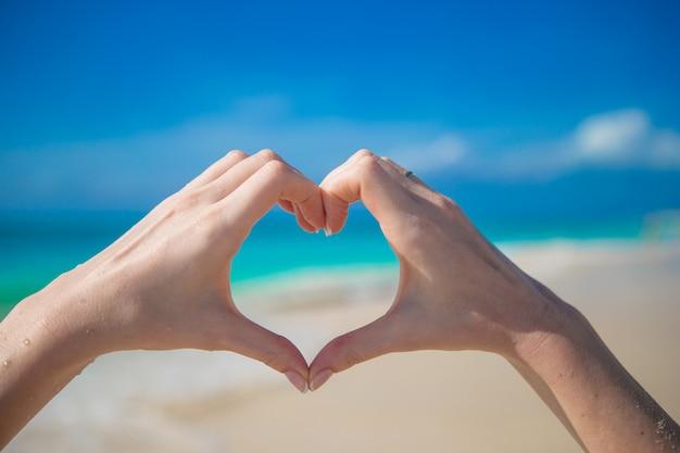 Símbolo do coração feito por mãos femininas na praia