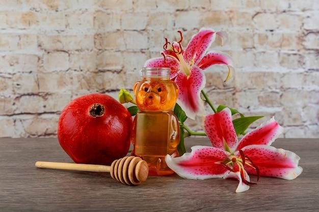 Símbolo do feriado judaico, lírio rosa, romãs frescas maduras com mel, símbolo do feriado judaico