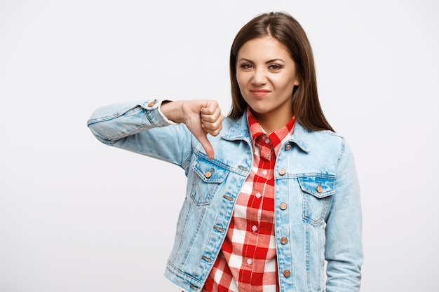 Símbolo do polegar para baixo. emoções negativas do show de uma linda mulher olhando direto