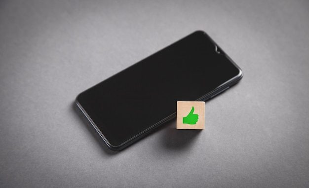 Símbolo do polegar para cima em um cubo de madeira com um smartphone