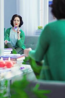 Símbolo especial. mulher alegre e simpática segurando uma carta de tarô enquanto vê seu reflexo no espelho