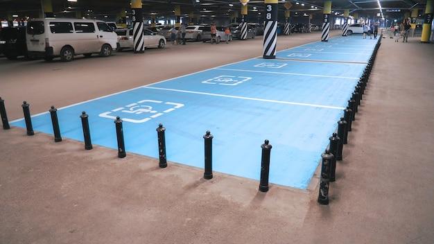 Símbolo internacional deficiente pintado em azul brilhante em um espaço de estacionamento do shopping.