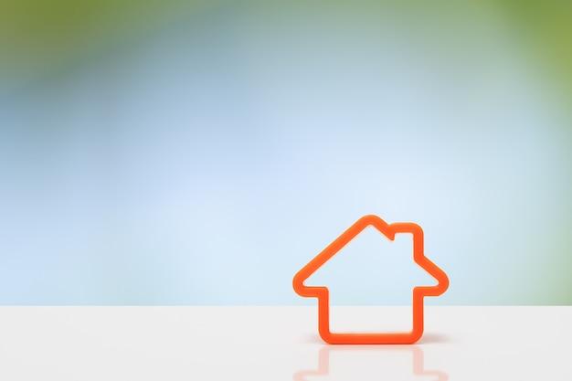 Símbolo laranja do ícone em casa. ícone de casa na mesa branca com fundo verde