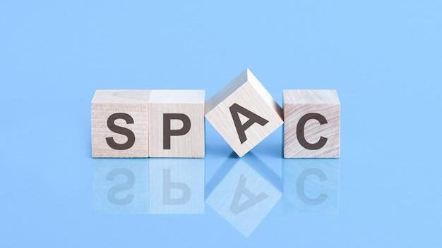 Símbolo spac. blocos de madeira com as palavras 'spac, empresas de aquisição de propósito especial' em um fundo azul bonito, copie o espaço. conceito de negócios.