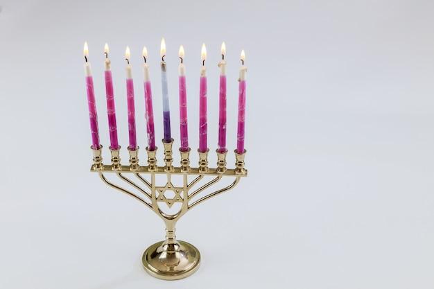 Símbolo tradicional hebraico menorá de hanukkah com velas acesas no festival judeu ortodoxo em fundo branco isolado