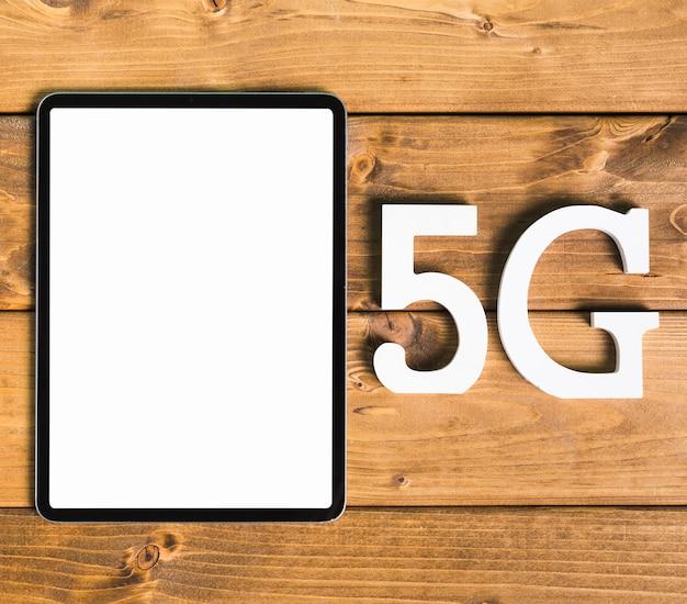 Símbolos 5g e tablet na mesa de madeira