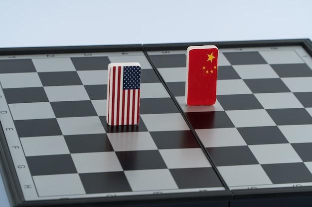 Símbolos da bandeira dos eua e da china no tabuleiro de xadrez. o conceito de jogo político.