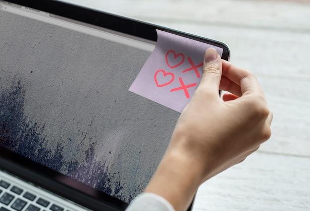 Símbolos de coração e beijo desenhados em uma nota auto-adesiva