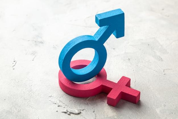 Símbolos de gênero de homem e mulher em um fundo cinza.