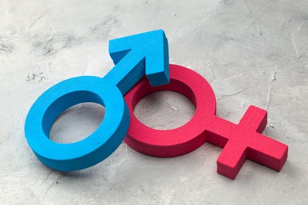 Símbolos de gênero de homem e mulher em uma superfície cinza.