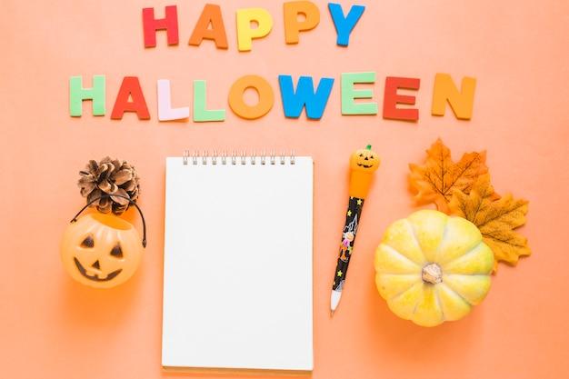 Símbolos de halloween perto de escrita e papelaria