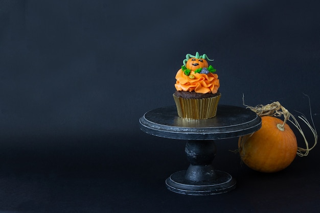 Símbolos de halloween, preparação para o feriado. cupcakes de abóbora laranja e decoração em madeira.