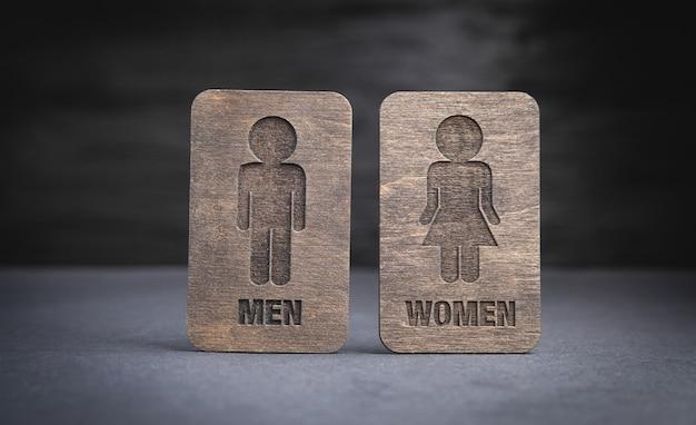 Símbolos de madeira de homens e mulheres no fundo preto.