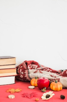 Símbolos de outono perto de manta e livros