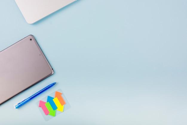 Símbolos de setas coloridas; celular; e caneta no pano de fundo azul