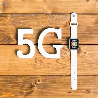 Símbolos decorativos 5g e relógio inteligente na mesa