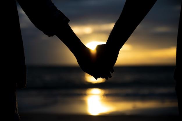 Símbolos do amor silhueta casal de homem e mulher mão segurando juntos