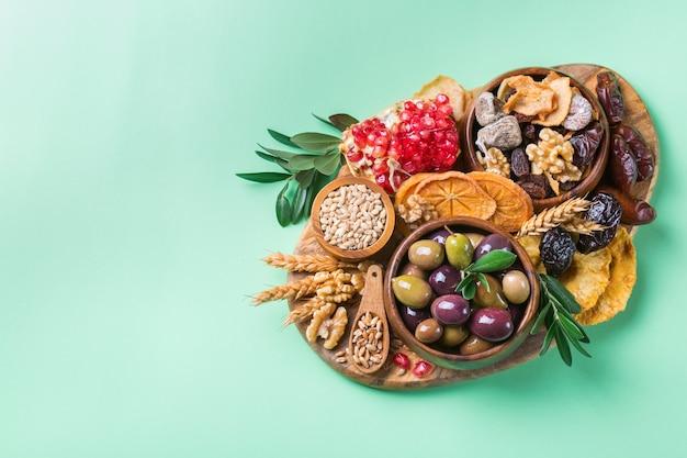 Símbolos do feriado judaico tu bishvat, rosh hashana, ano novo das árvores. mistura de frutas secas, tâmara, figo, uva, cevada, trigo, azeitona, romã. copiar espaço plano de fundo verde