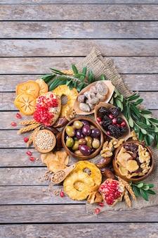 Símbolos do feriado judaico tu bishvat, rosh hashana, ano novo das árvores. mix de frutas secas, tâmara, figo, uva, cevada, trigo, azeitona, romã em uma mesa de madeira. copiar espaço plano de fundo