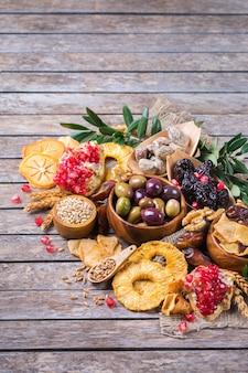 Símbolos do feriado judaico tu bishvat, rosh hashana, ano novo das árvores. mix de frutas secas, tâmara, figo, uva, cevada, trigo, azeitona, romã em uma mesa de madeira. copie o fundo do espaço