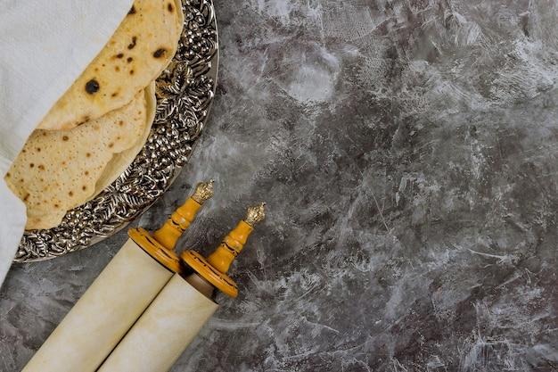 Símbolos tradicionais da matzá do feriado judaico com pão da páscoa no rolo da torá