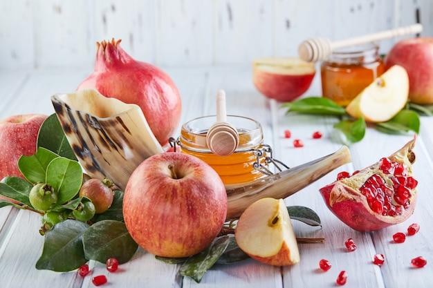 Símbolos tradicionais: pote de mel e maçãs frescas com romã e shofar-chifre em madeira branca.