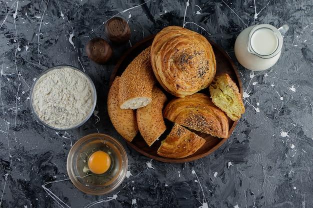 Simit de bagel turco picado com ovo de galinha cru e uma jarra de leite.