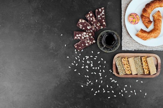 Simit turco com biscoitos e um copo de chá, vista superior.
