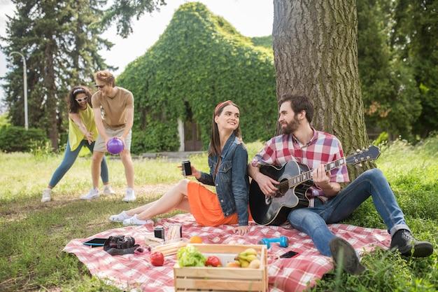 Simpatia. um cara barbudo com uma guitarra e uma garota de cabelos compridos com uma bebida olhando um para o outro sentados sob uma árvore e amigos com uma bola atrás