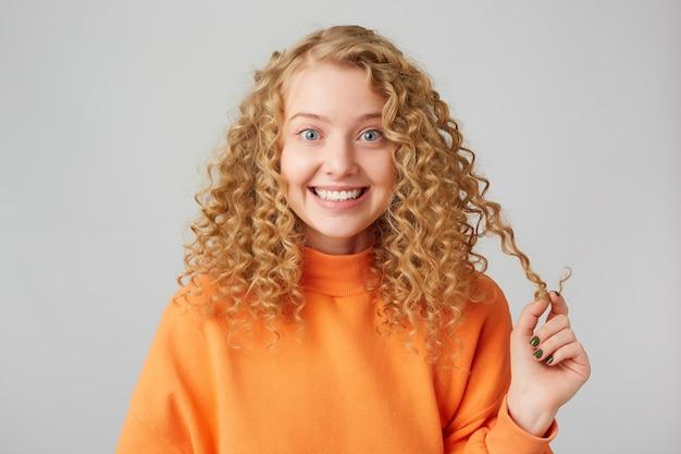 Simpática atraente alegre jovem loira sorri sinceramente, satisfeita, de bom humor