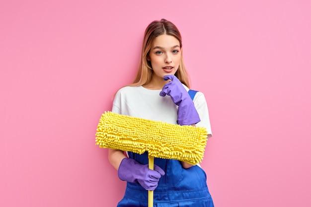Simpática dona de casa de bom humor segurando o equipamento de limpeza, pano no chão, usando macacão de uniforme azul